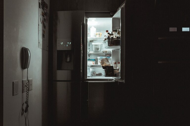 Opening a fridge at night.