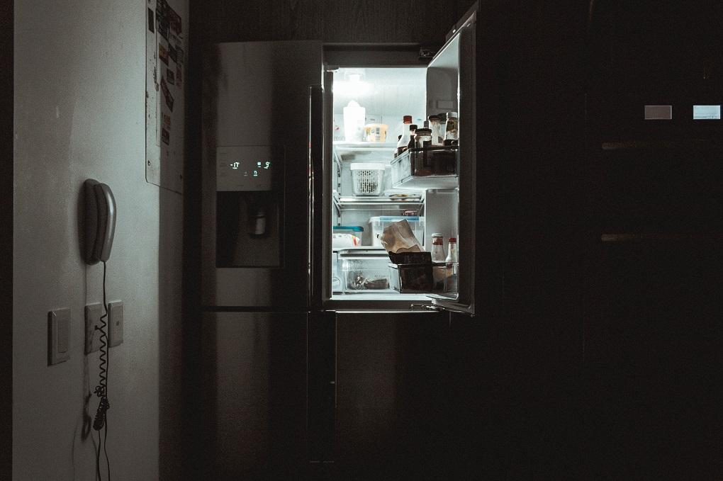 Opening a fridge at night.