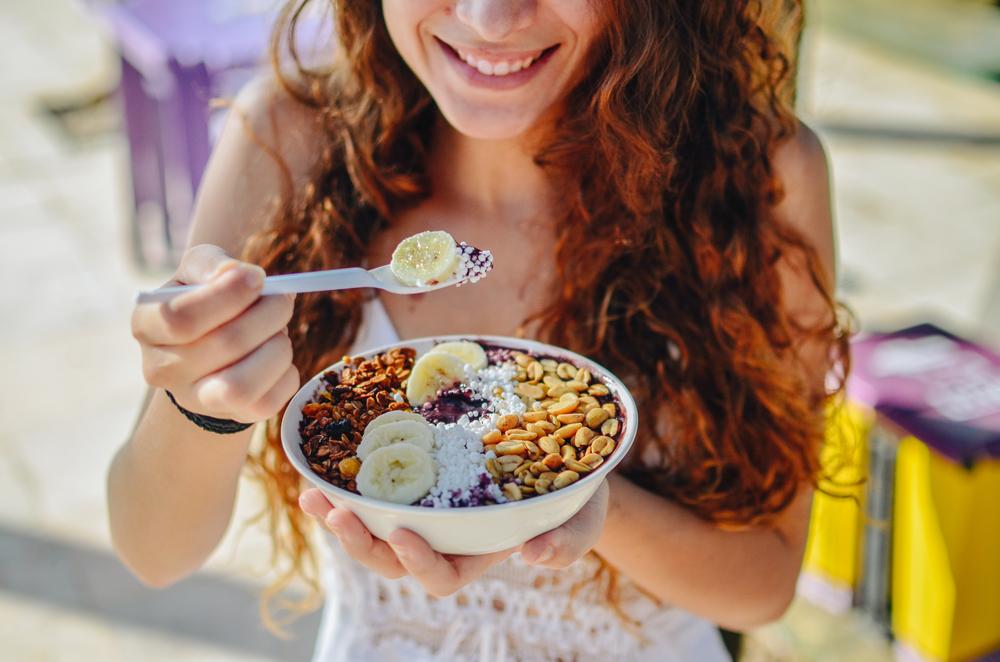 Woman enjoying acai bowl.